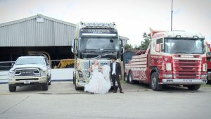 bride and groom posing for the wedding photographer in front of the custom paint gold blockley and sons truck in drighlington