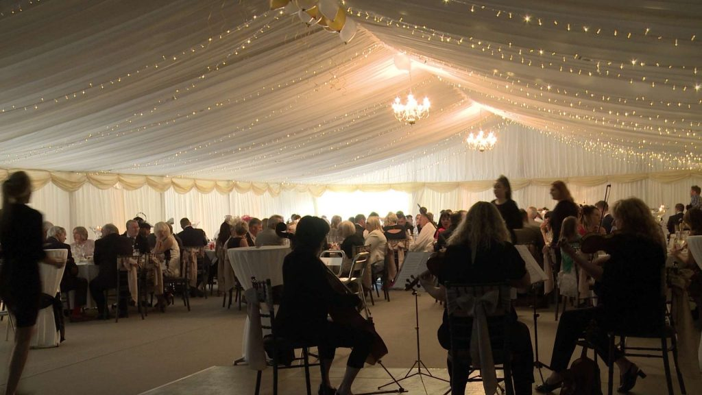 stunning marquee inside a working farm barn with fairy lights and a string quartet during the wedding breakfast