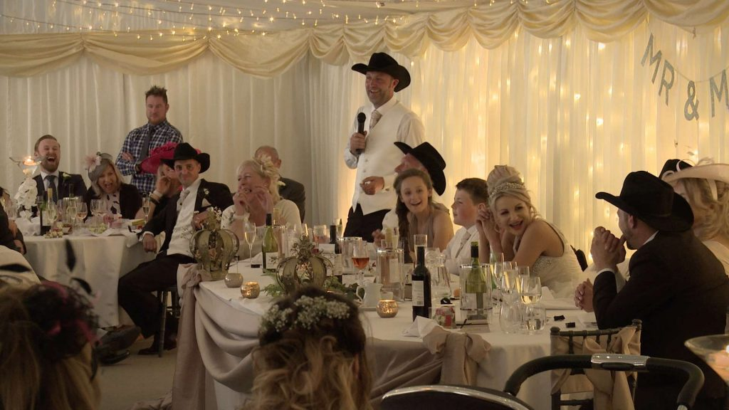 groom making a speech during his marquee wedding on a working farm