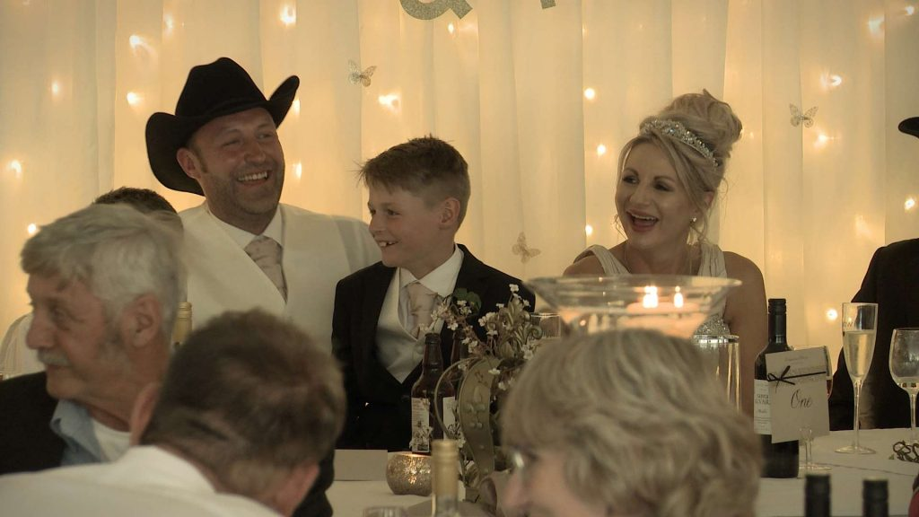 bride and groom laughing during the best man speech at their drighlington wedding