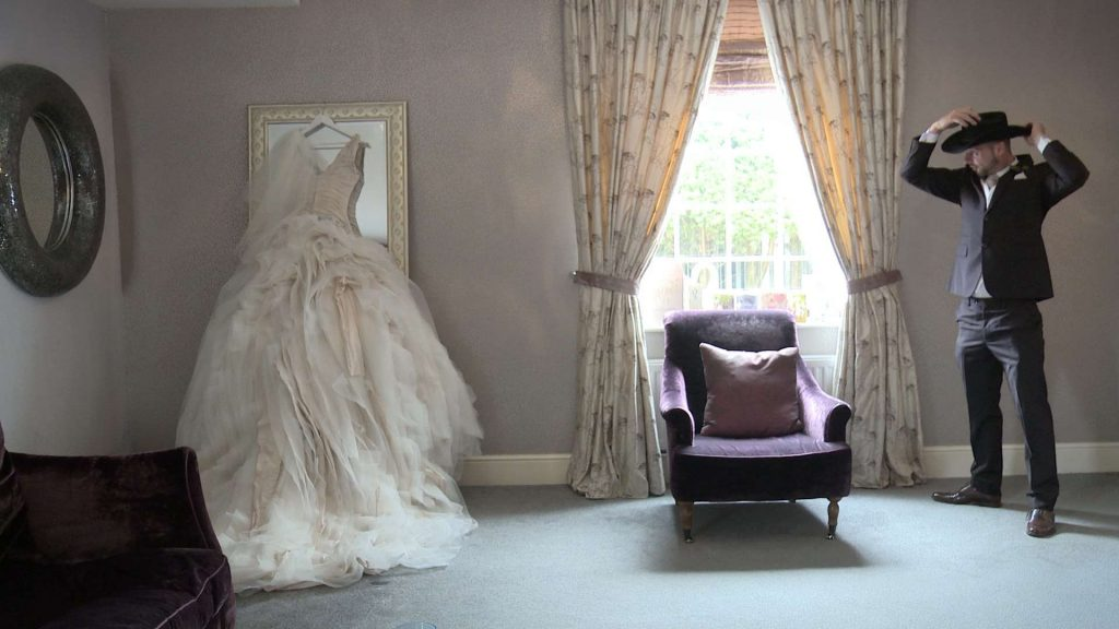 Ian Stuart blush layered wedding dress hanging up on a full length mirror for the wedding video in West Yorkshire