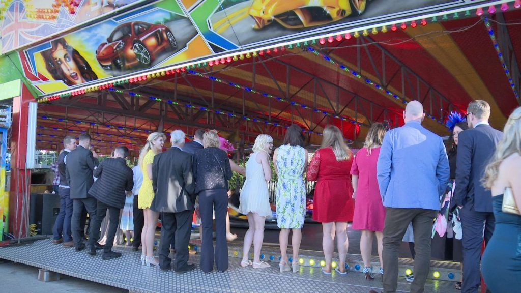 wedding guests waiting to have a go on the fairground dodgem bumper cars