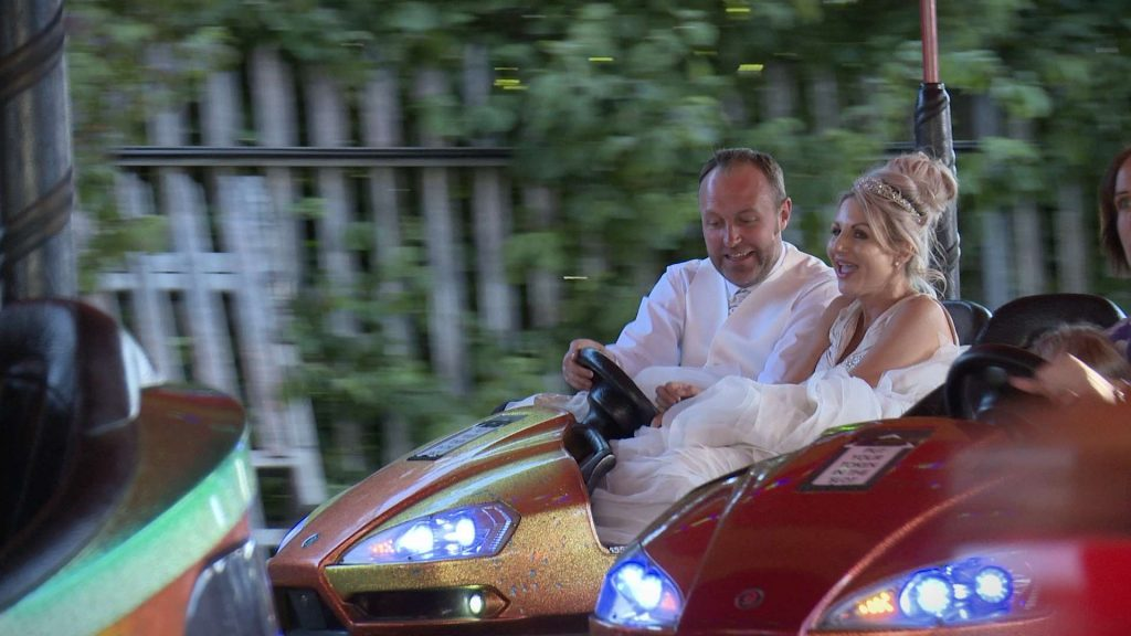 bride and groom having a go on the dodgem bumper cars during their fairground wedding reception in drighlington