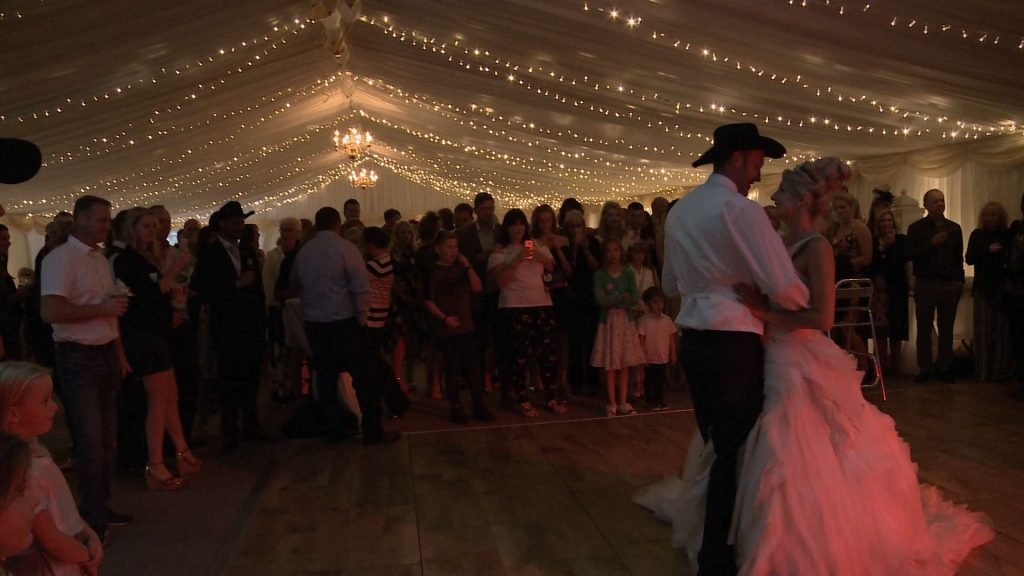 bride and groom having a first dance to Prince with the bride wearing Ian Stuart and Groom a Stetson