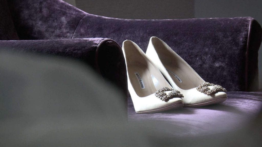 Manolo blahnik wedding shoes in champagne colour on a purple velvet chair at a wedding in drighlington