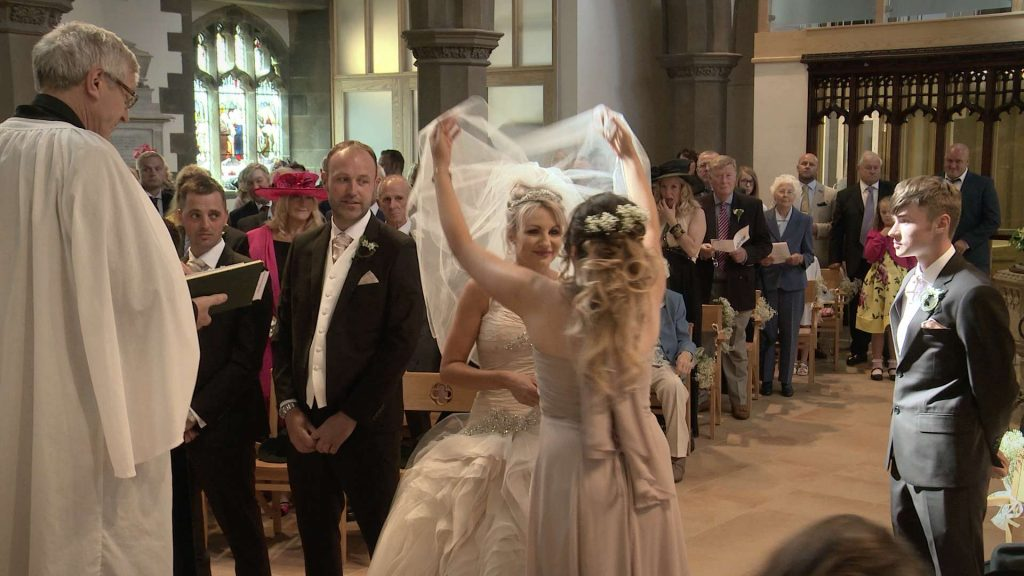 bridesmaid lifting the brides veil during their wedding ceremony at St Pauls in drighlington