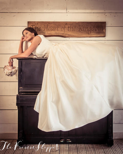 Bride casually laying on a piano at Bashall Hall in her big wedding dress holding a unicorn inspired Bouquet