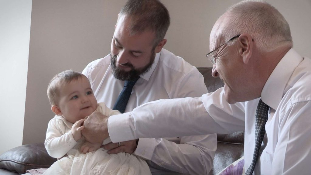 dad and grandad getting giggles off baby charlotte before her christening