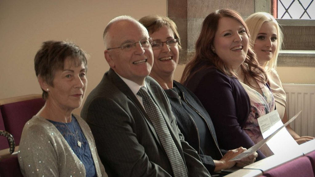 grandparents and aunties laughing sat in the pews at Rhyl church during a christening