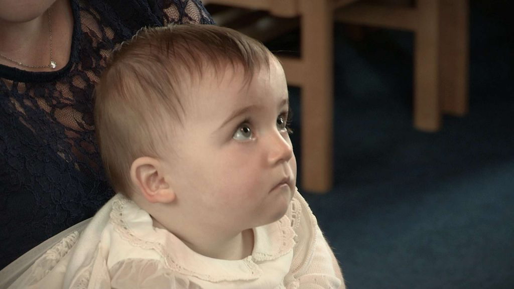 baby girl during christening looking very serious on the video