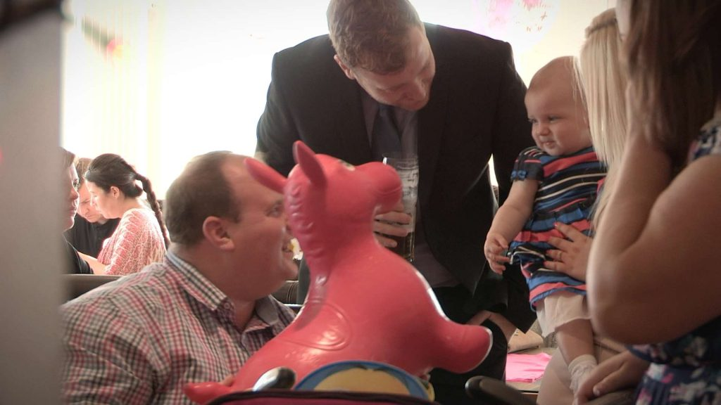 parents trying to make a baby girl laugh with an inflatable horse at a christening in rhyl