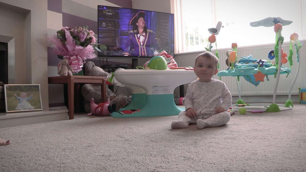 baby girl sat in her living room waiting for her mummy and daddy on video for her own christening video