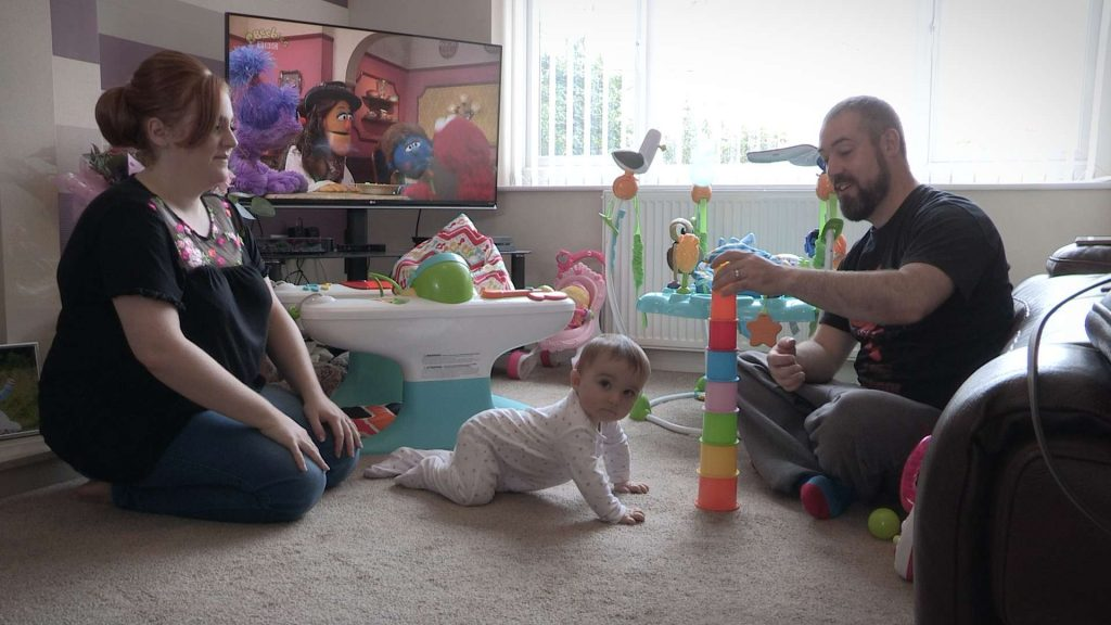 baby girl playing with parents in their home before getting ready for her Christening video in Rhyl