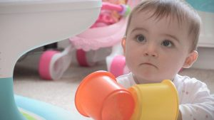 baby charlotte playing with stacking blocks at home in Ryhl with her Mum and Dad before her Christening