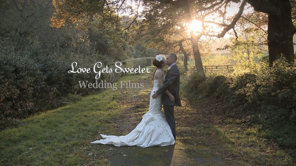 Bride and Groom having a cuddle and kiss with the winter sun low behind them peeking through the trees at Whitley Hall for the wedding video