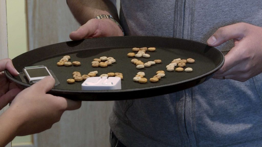 the best man holds a tray with cheerios spelling out I Love You to remind the bride of the grooms romantic proposal before they get married at On The 7th in Media City Salford for their wedding video