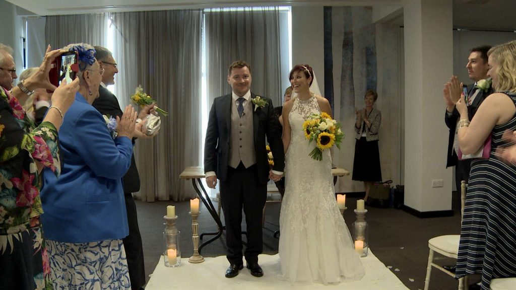 The bride and groom are getting ready to walk down the aisle towards the wedding videographer after being married and look very happy and excited as their wedding guests stand up to cheer. They have a white carpet aisle and she holds an oversized sunflower bouquet