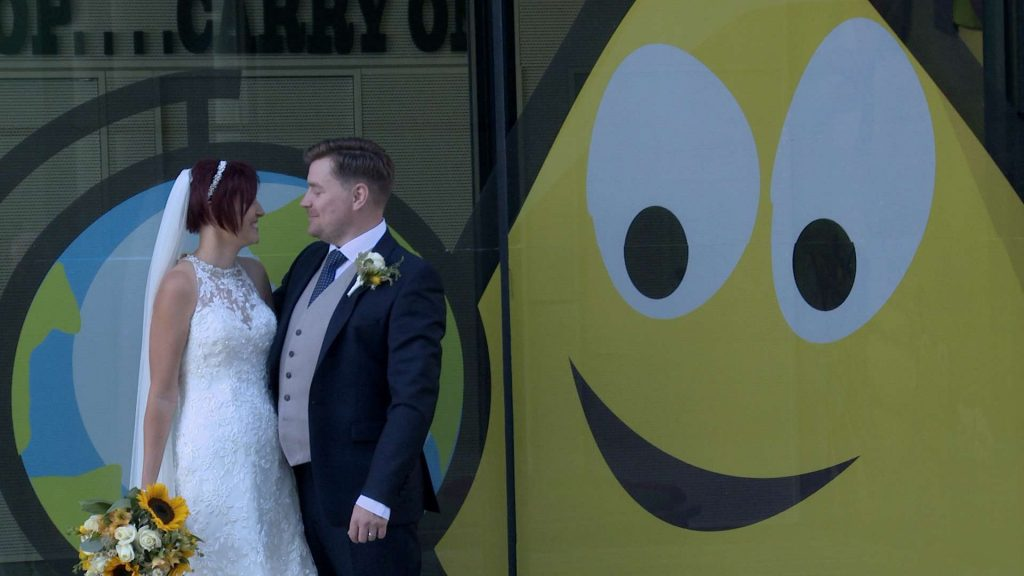 Bride and Groom standing in front of the CBeebies window in Salford Media City posing for a fun wedding photograph with Mick Cookson. Bride holds her bright oversized wedding bouquet of roses and sunflowers
