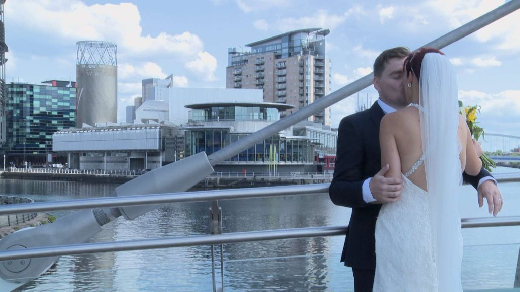 groom kisses his bride on the lowry bride in Salford