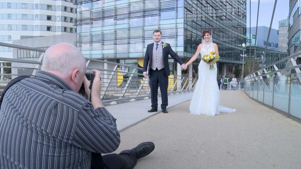 Mick Cookson sits on the floor of lowry bridge to take a fun photo of the bride and groom