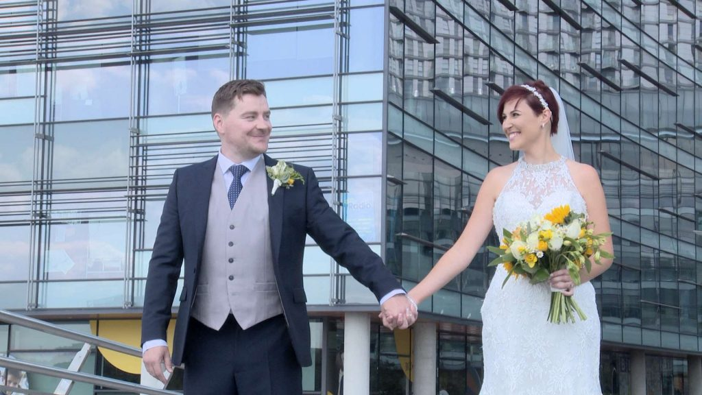 the bride and groom hold hands and look at each other for their wedding photographs at Media City Manchester