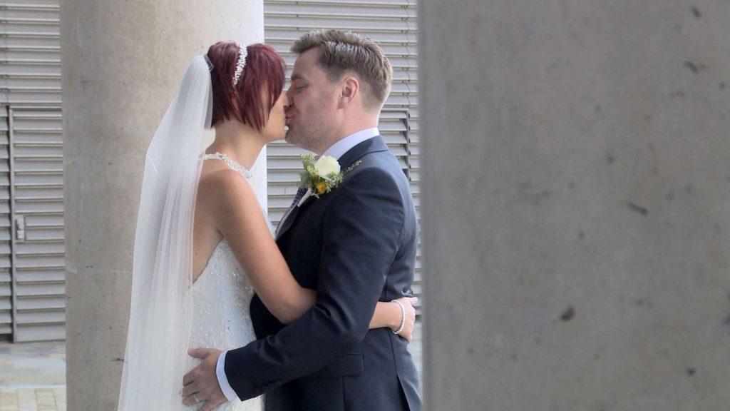 The bride and groom enjoy a kiss for the photographer and videographer outside media city