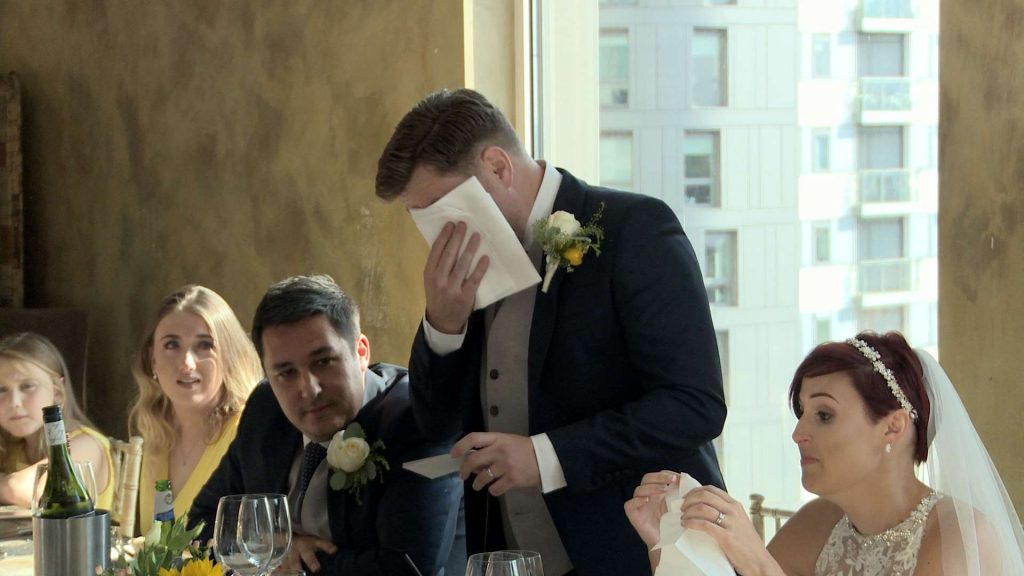 a video still of the groom wiping away his tears after an emotional part of his wedding speech