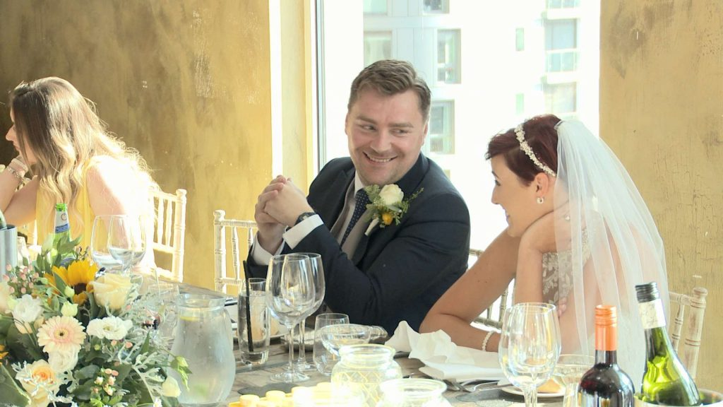 the bride and groom smile at each other during the wedding speeches at On The 7th