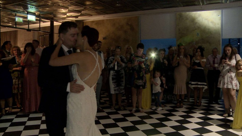 our newlyweds enjoy their first dance surrounded by friends and family at their wedding at On The 7th