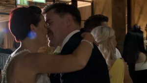 the bride and groom have a kiss on the black and white dancefloor at on the 7th