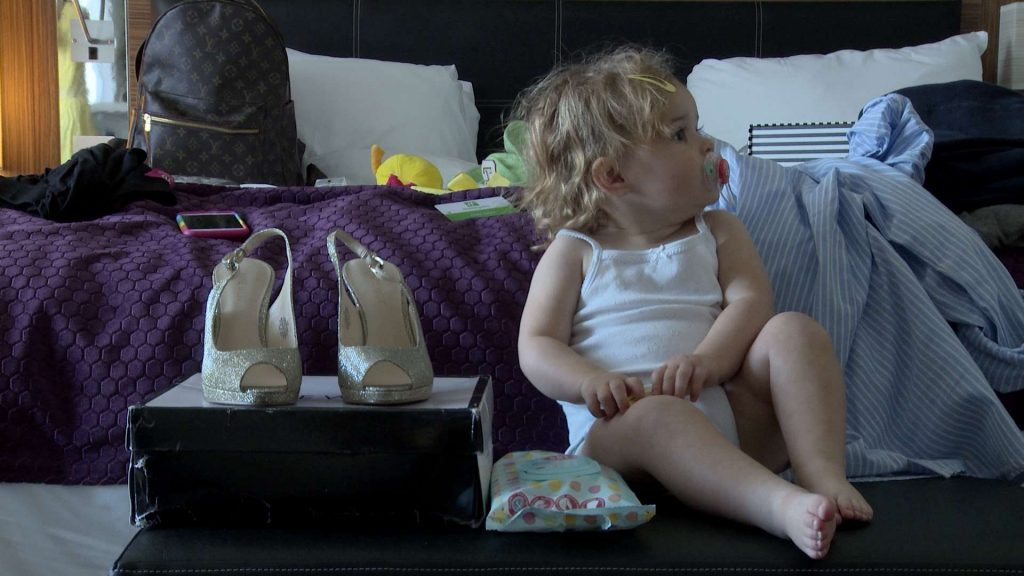 The cute flower girl sits in her white vest next to the brides very sparkly wedding shoes during the wedding morning in Manchester