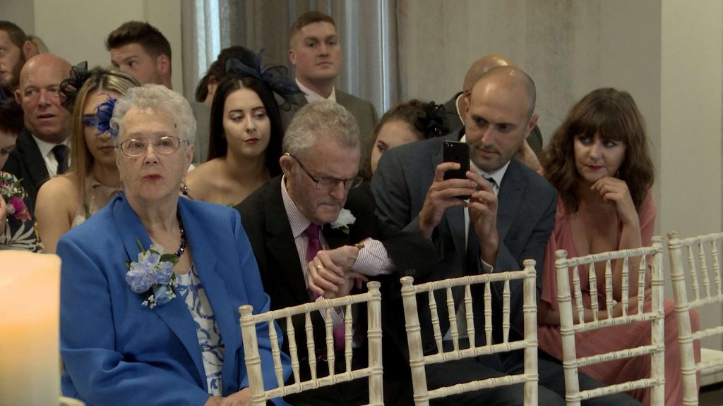 wedding guests check their watches and take photos on their phones as they wait for the Bride to arrive for a wedding inside the members club On The 7th