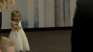 a cute little flower girl wearing white waits and poses at the top of the wedding aisle on the wedding video at her dads wedding at On The 7th