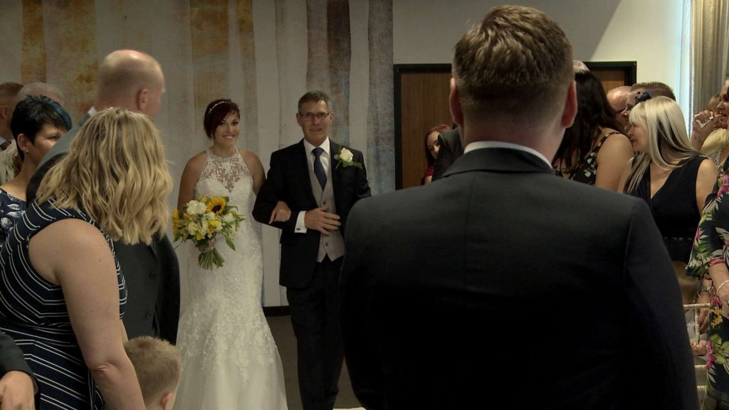 Our short haired bride walks down the aisle with her dad holding a sunflower and white rose bouquet
