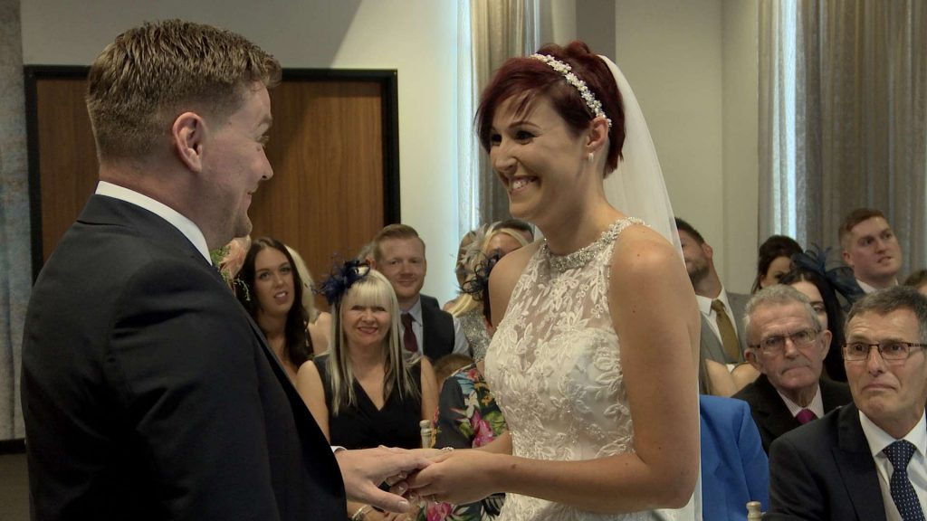 The bride and groom smile and laugh at each other on the wedding video as they exchange their wedding rings during an intimate ceremony at On The 7th in Media City