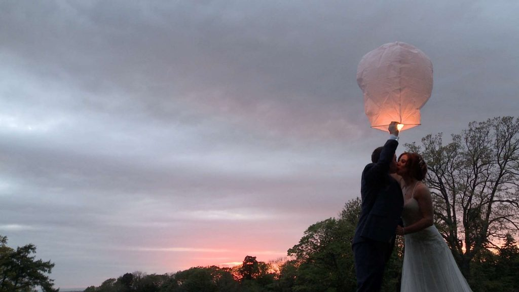 a bride and groom have a kiss before their chinese lantern floats off in to the beautiful sunset in Wyresdale Park
