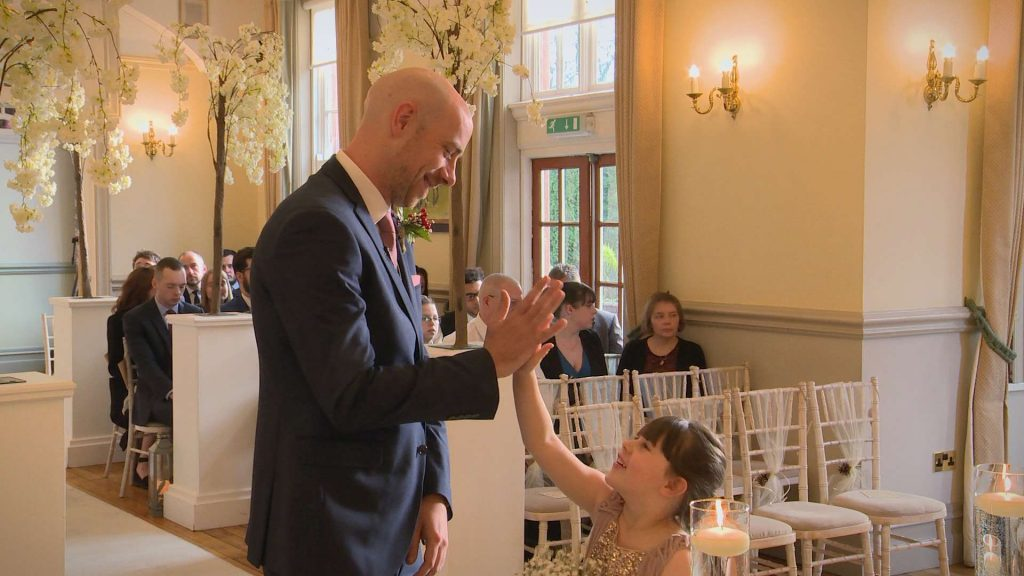The Groom gives his daughter and flower girl a high five as they wait for the bride to arrive at their wedding ceremony at Nunsmere Hall