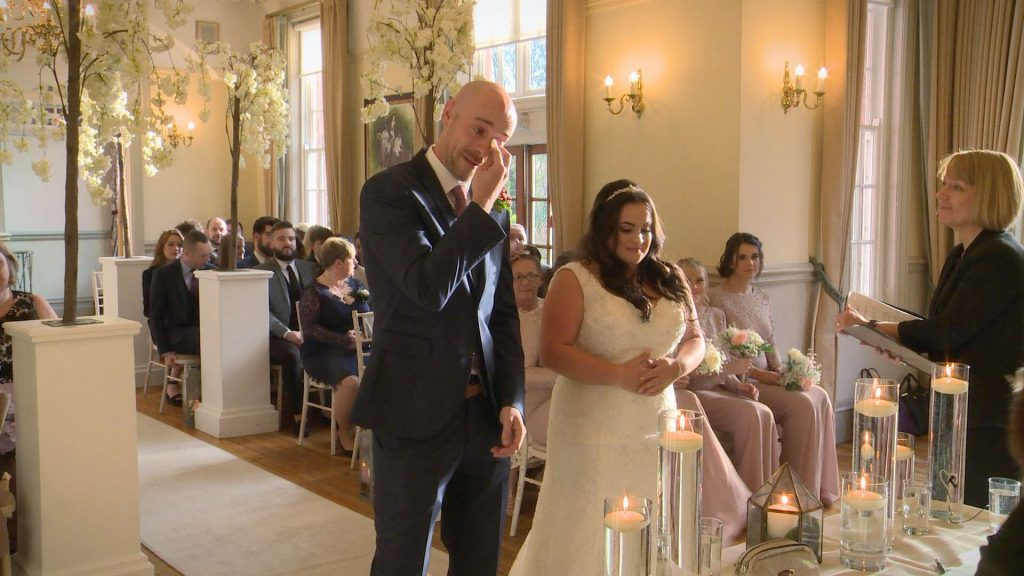Caught on their wedding video the groom uses a tissue to wipe away his tears after seeing his bride walk down the aisle for their Winter Nunsmere Hall winter wedding