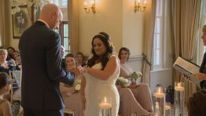 the groom puts the wedding ring on his bride as they say their vows at Nunsmere Hall