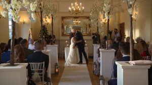 the bride and groom kiss as their guests applaud them being husband and wife at Nunsmere Hall