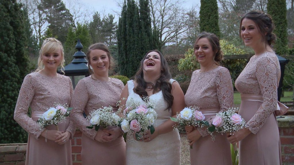 The bride and bridesmaids laugh out loud with their wedding videographer as they have formal photos taken outside nunsmere hall wearing blush pink ASOS bridesmaid dresses and holding faux rose bouquets