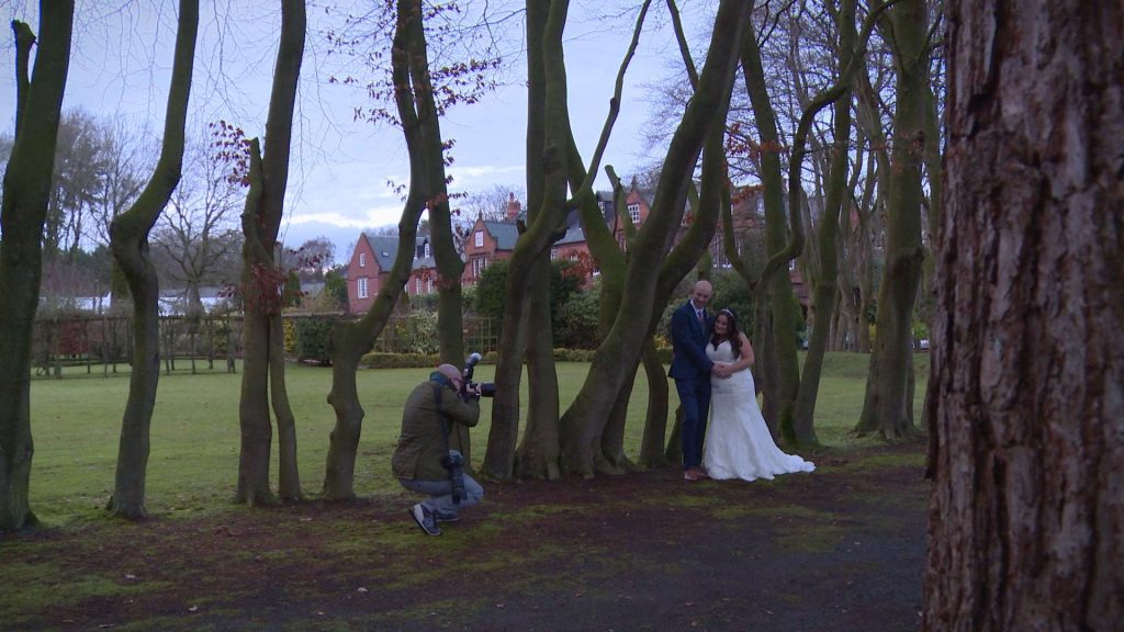 a wedding photographer crouches down to take a photo of the bride and groom posing outside Nunsmere Hall on a chilly December day