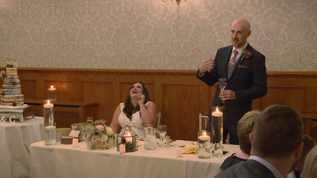 the groom makes the bride laugh out loud during his wedding speech on their wedding video the table looks romantic with candles
