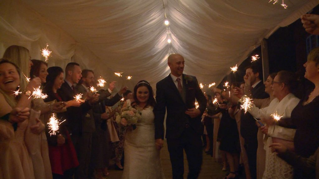 the bride and groom walk through a tunnel of guests towards the wedding videographer waving sparklers during the evening reception at Nunsmere Hall in Cheshire