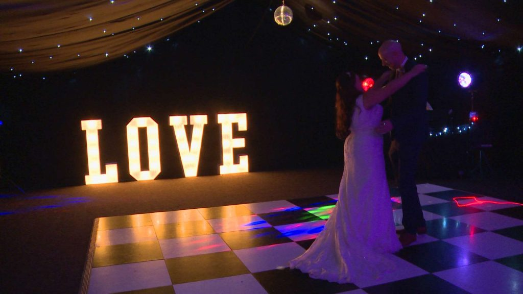 a bride and groom do their first dance for the wedding video on a black and white dance floor with illuminated LOVE letters behind them