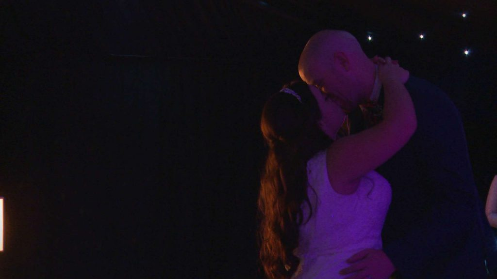 the bride and groom kiss during their first dance at their winter wedding at Nunsmere