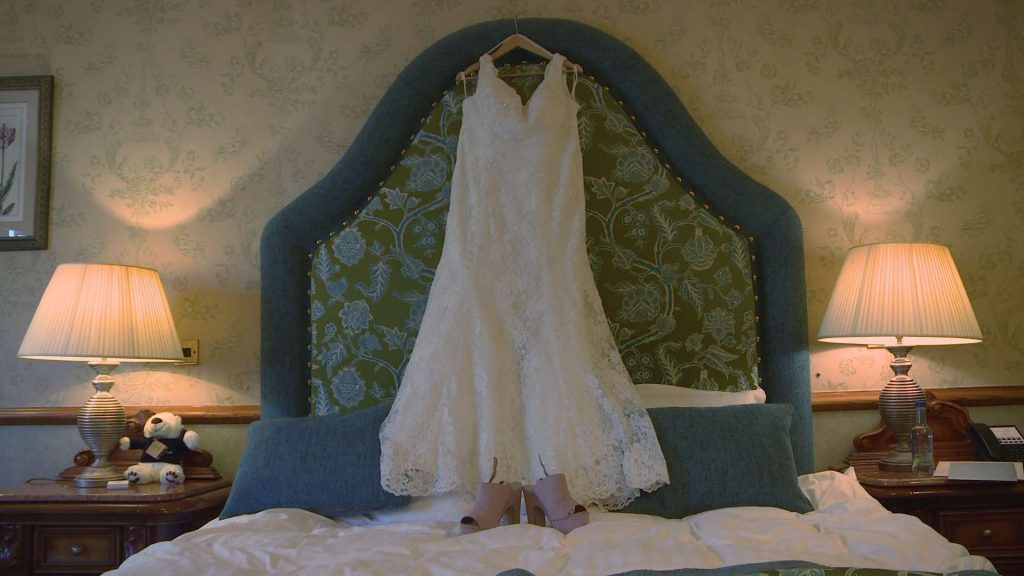 A brides dress hangs waiting for its bride in a bedroom suite at Nunsmere Hall