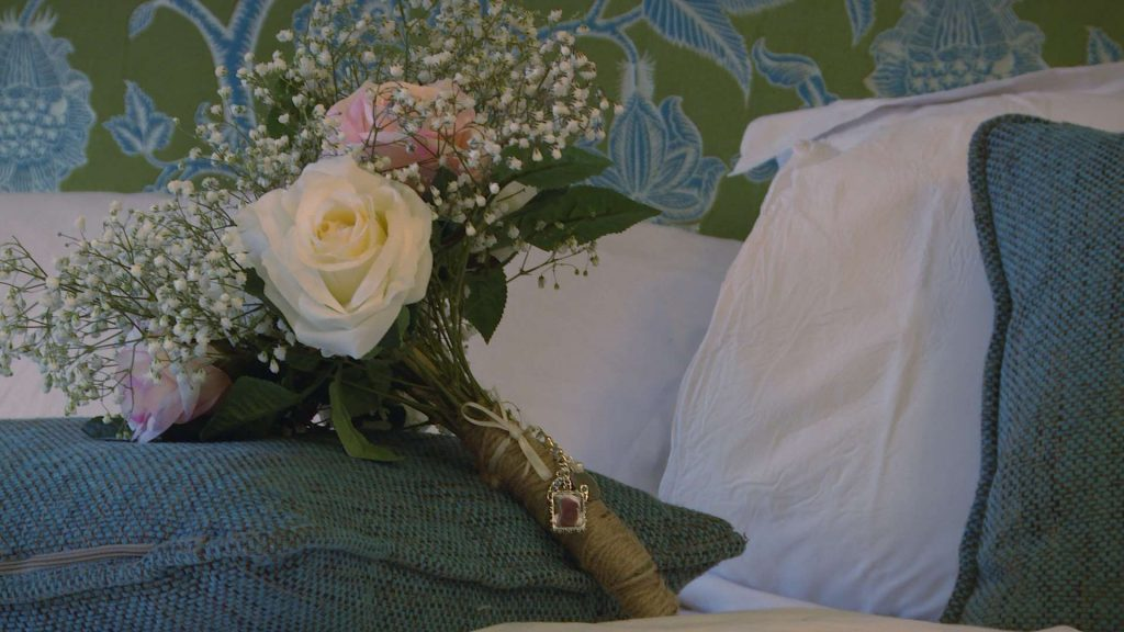 A silk flower bouquet of pinks and creams with gypsy grass lays on the green pillow. It's hand tied with brown string and has a pendant of the brides dad to remember him on her wedding day