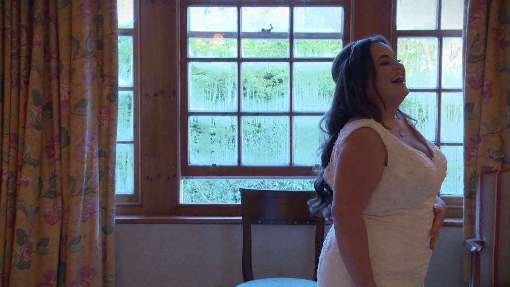 The bride laughs as she tries to pose for her wedding photographer at Nunsmere Hall