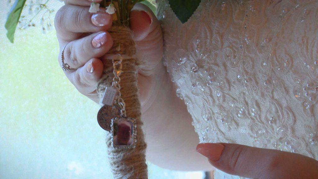 a close up shot of the locket pendant of the brides Dad tied on to her hand tied silk bridal bouquet